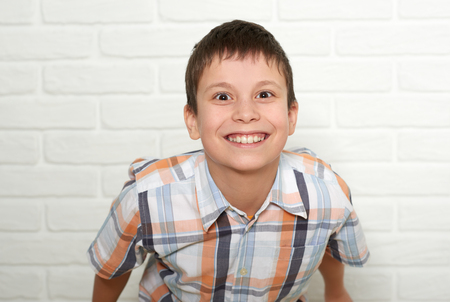 Portrait of a emotional boy standing near white brick wall, dressed in a plaid shirt