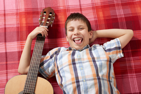 boy playing music on guitar, lies on a red checkered blanket, top view Stock Photo