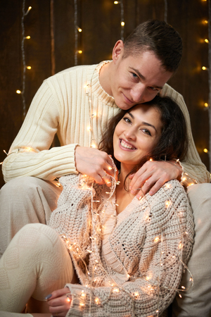 young couple together in christmas lights and decoration, dressed in white, fir tree on dark wooden background, romantic evening, winter holiday concept Imagens