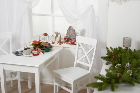white room interior with christmas decoration, window, table and chair