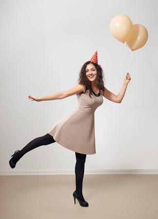 happy young woman or teen girl in brown dress with helium air balloons