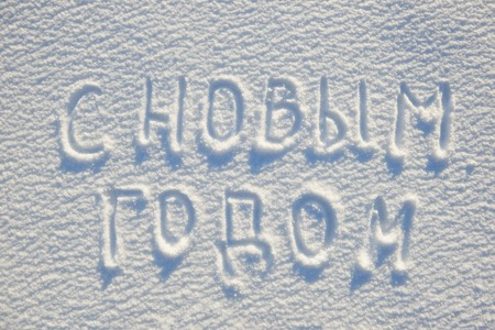 Happy New year text written on russian language on snow for texture or background - winter holiday concept. Banco de Imagens
