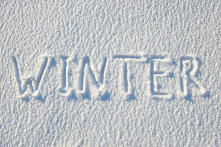 Winter text written on snow for texture or background - winter holiday concept. Sunny day, bright light with shadows, flat lay, top view, clean and nobody