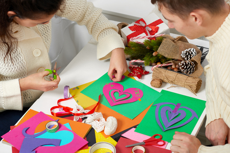 young couple making decorations from paper for Valentine day, top view - romantic and love concept