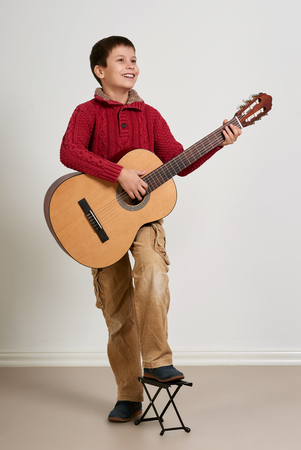 Boy posing with acoustic guitar Stock Photo