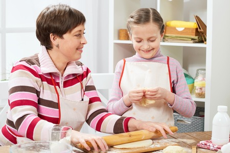 Mother and daughter cooking at home, making the dough for buns Standard-Bild
