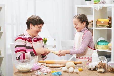 Mother and daughter cooking at home, making the dough for buns Imagens