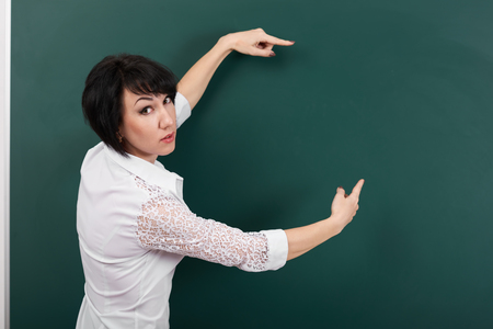woman teacher shows on a blackboard anything, blank space for text and graphics, green background, Studio shot