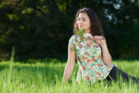 beautiful girl sitting on a glade in the park, bright sun and shadows on the grass Stock Photo