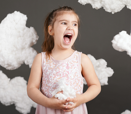 girl playing with clouds, shot in the studio on a gray background Archivio Fotografico - 101589873