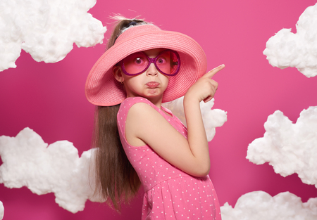 fashionable girl posing on a pink background of clouds, pink dress and hat
