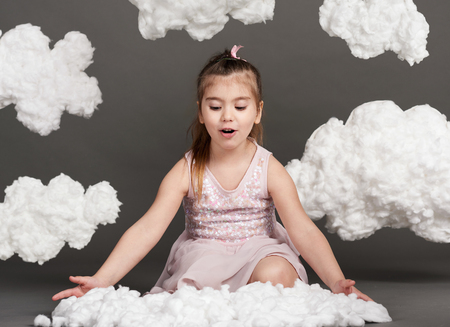 girl playing with clouds, shot in the studio on a gray background