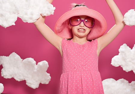 fashionable girl posing on a pink background with clouds, pink dress and hat