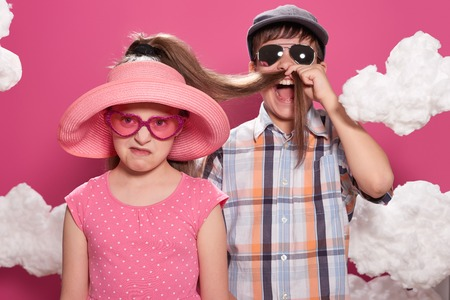 fashionable girl and boy posing on a pink background with clouds Reklamní fotografie