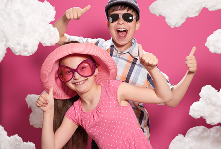 fashionable girl and boy posing on a pink background with clouds Stok Fotoğraf