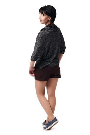 young woman posing in studio on white background, wearing brown shorts and shirt