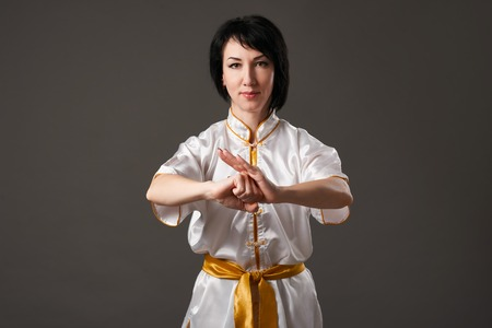 Young woman practicing tai chi chuan. Chinese management skill Qi's energy. Gray background, studio shoot.