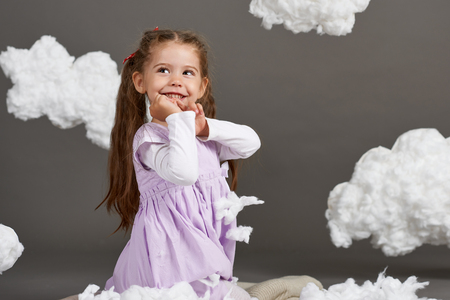 girl playing with clouds, shooting in the studio on a gray background, happy childhood concept