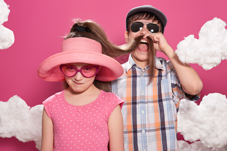 fashionable girl and boy posing on a pink background with clouds Stock Photo
