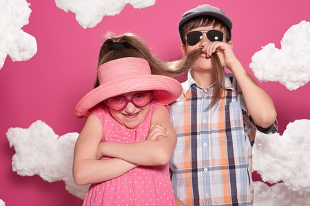 Fashionable girl and boy posing on a pink background with clouds