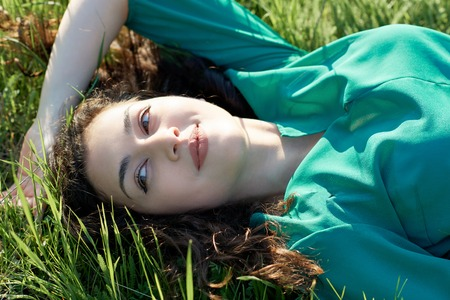beautiful girl lying on the grass at sunny day, face closeup, summer forest, bright landscape with shadows