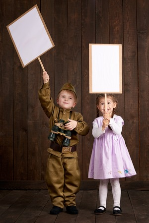 Children boy are dressed as soldier in retro military uniforms and girl in pink dress. They're holding blank posters for veterans portraits.