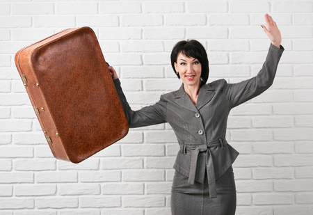 business woman dressed in a gray suit with suitcase stay in front of a white wall