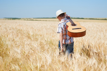 child boy with guitar is in the yellow wheat field, bright sun, summer landscape Imagens