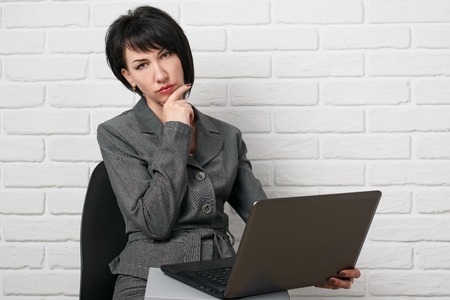 business woman with laptop and folders, dressed in a gray suit poses in front of a white wall Stock Photo