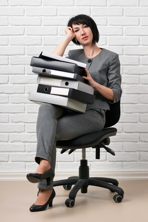 business woman with folder, dressed in a gray suit poses in front of a white wall