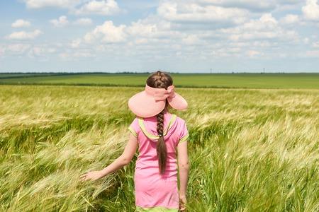 child walking through the wheat field, bright sun, beautiful summer landscape