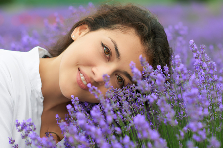 young woman is in the lavender field, beautiful portrait, face closeup, summer landscape with red poppy flowers