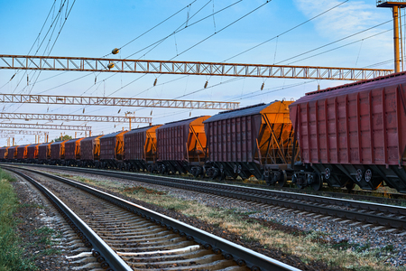 Railroad infrastructure during beautiful sunset and colorful sky, railcar for dry cargo, transportation and industrial concept Stock Photo