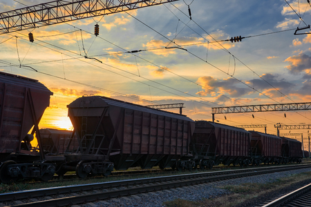 Railroad infrastructure during beautiful sunset and colorful sky, railcar for dry cargo, transportation and industrial concept