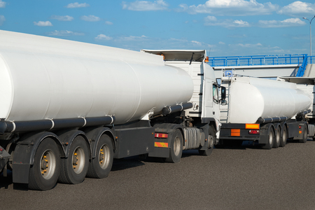 White tank trucks on the road, clear space on the cistern side, oil transportation concept