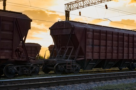 Railcar for dry cargo during beautiful sunset and colorful sky, railroad infrastructure, transportation and industrial concept Stock Photo