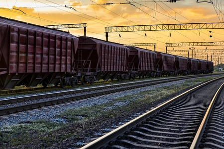 Railcar for dry cargo during beautiful sunset and colorful sky, railroad infrastructure, transportation and industrial concept