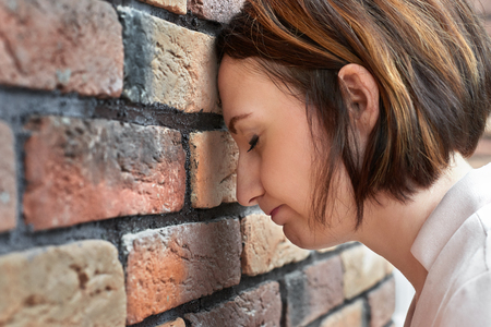 the young girl put her head to the brick wall, trouble concept Фото со стока