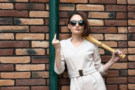 young girl with baseball bat shows a fuck gesture and poses on the back street by a brick wall Stock Photo