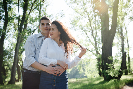 young couple walking in the forest, summer nature, bright sunlight, shadows and green leaves, romantic feelings