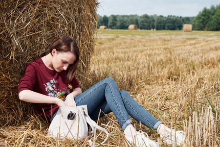 young girl having fun in the field, sits in a haystack and relaxing Stock Photo