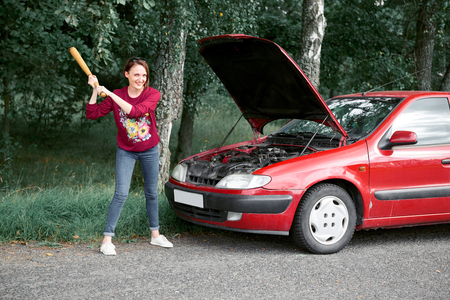 a young woman is near a broken car, has stress and rage, wants to smash her car with a baseball bat