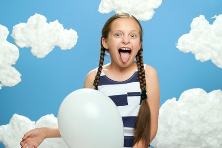 girl dressed in striped dress posing on a blue background with cotton clouds, white air balloon, the concept of summer and happiness