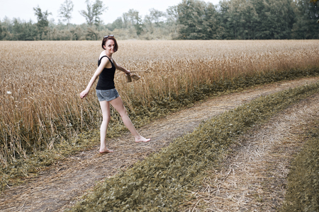 young girl walking barefoot on the ground road through field and forest, the concept of summer and travel Stockfoto