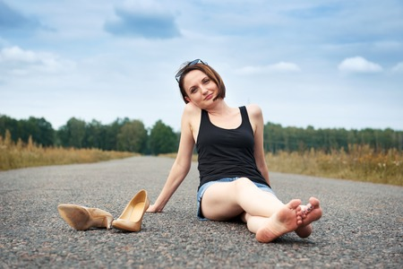 young girl sitting barefoot on the road, she left her shoes on the road and forgot them, the concept of summer and travel Stockfoto