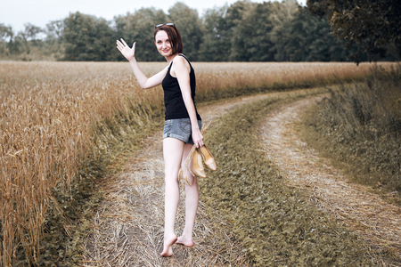 young girl walking barefoot on the ground road through field and forest, the concept of summer and travel Stock Photo