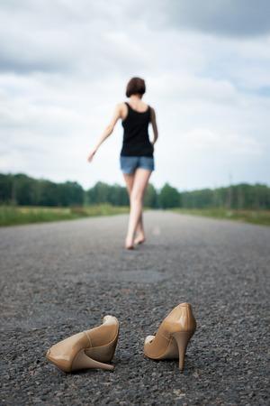jong meisje liep op blote voeten op de weg, ze liet haar schoenen op de weg liggen en vergat ze, het concept van zomer en reizen