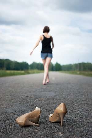 young girl walking barefoot on the road, she left her shoes on the road and forgot them, the concept of summer and travel