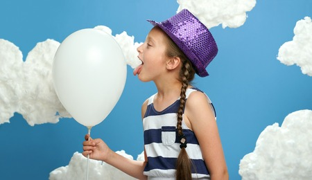girl dressed in striped dress and color hat posing on a blue background with cotton clouds, white air balloon, the concept of summer, happiness and holiday Stock Photo