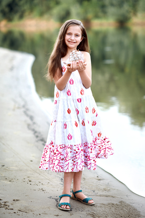 girl playing with a toy sailing ship by the river